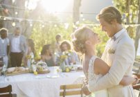 Young couple dancing during wedding reception in domestic garden — Stockfoto