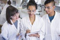 Étudiants en blouse de laboratoire discutant de notes en classe de laboratoire de sciences — Photo de stock