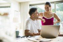 Casal sorridente, falando para o laptop na cozinha de manhã — Fotografia de Stock