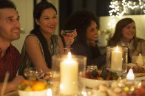 Smiling friends drinking champagne at candlelight Christmas dinner — Stock Photo