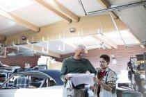 Vater und Sohn Überprüfung Pläne in Autowerkstatt — Stockfoto