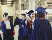 College graduates in cap and gown holding diplomas — Stock Photo