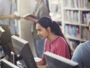 Étudiante ciblée qui fait des recherches à l'aide d'un ordinateur dans une bibliothèque — Photo de stock