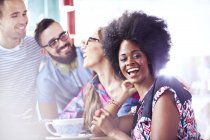 Portrait of laughing woman hanging out with friends in cafe — Stock Photo