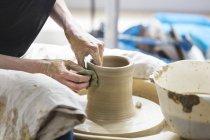 Mulher usando roda de cerâmica no estúdio — Fotografia de Stock