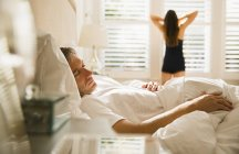Wife stretching at morning window behind husband sleeping in bed — Stock Photo