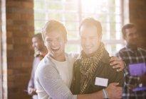 Sonrientes joven hombres abrazándose en el seminario - foto de stock