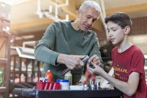 Father teaching son how to use tools in auto repair shop — Stock Photo