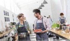 Coppia che trasporta cibo in cucina — Foto stock