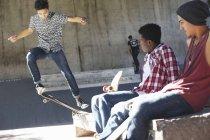 Amigos viendo adolescente haciendo acrobacias en skate park - foto de stock