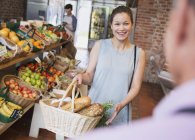 Woman with basket smiling at grocery store worker — Stock Photo