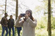 Женщина в походе с камерой в лесу — стоковое фото