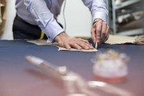 Tailor marking fabric in menswear workshop — Stock Photo