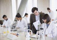 Professeur de sciences aidant un étudiant menant une expérience scientifique en classe de laboratoire de sciences — Photo de stock