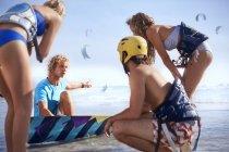 Man teaching friends kiteboarding on sunny beach — Stock Photo