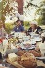 Друзі, насолоджуючись обідом на патіо таблиці — стокове фото