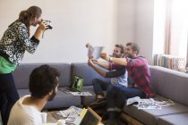 Creative businessmen with proofs posing for coworker with instant camera — Stock Photo