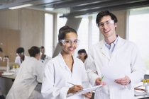 Portrait confident college students in lab coats in science laboratory classroom — Stock Photo