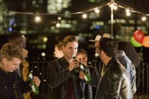 Young men drinking beer at rooftop party — Stock Photo