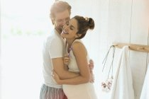 Affectionate pregnant couple hugging in sunny bathroom — Stock Photo