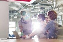 Gens d'affaires créatives réunis au portable au bureau ensoleillé — Photo de stock