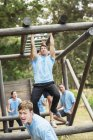 Determined man crossing monkey bars on boot camp obstacle course — Stock Photo