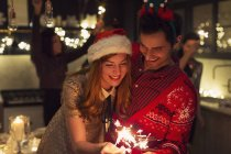 Playful couple with Christmas sparklers — Stock Photo