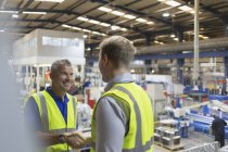 Smiling supervisor and worker handshaking in steel factory — Stock Photo