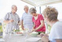 Casais seniores preparando o almoço no pátio — Fotografia de Stock