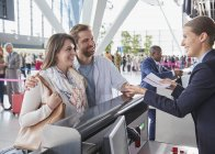 Customer service representative helping couple at airport check-in counter — Stock Photo