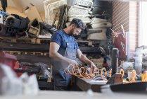 Mécanicien en utilisant des équipements à établi dans l'atelier de réparation automobile — Photo de stock