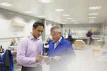 Gerente e ingeniero mirando el portapapeles en la oficina de la fábrica de acero - foto de stock
