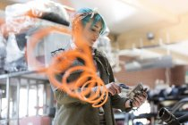 Jeune mécanicien femelle aux cheveux bleus à l'aide de matériel en atelier de réparation automobile — Photo de stock