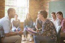 Група дивляться чоловік і жінка говорити в групової терапії сесії — стокове фото