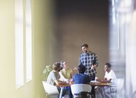 Casual businessman leading meeting at office table — Stock Photo