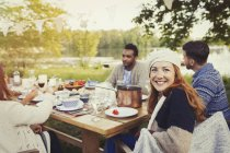 Portrait smiling woman enjoying lunch at lakeside patio table — Stockfoto