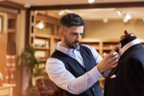 Tailor adjusting tie on dressmakers model in menswear shop — Stock Photo