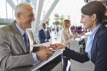 Клиент службы представитель помогая бизнесмен в аэропорту у стойки регистрации — стоковое фото