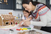 Mother and daughter decorating gingerbread house — Stock Photo