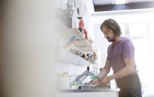 Человек, мытья инструментов на раковину в арт-студии — стоковое фото