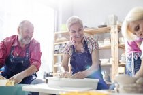 Smiling senior couple using pottery wheels in studio — Stock Photo