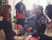 Amici ridenti che aprono i regali di Natale in salotto — Foto stock