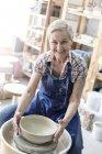 Portrait smiling senior woman using pottery wheel in studio — Stock Photo