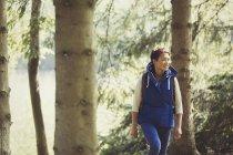 Усміхається жінка походи в лісі — стокове фото