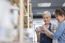 Donne che esaminano ciotola in studio di ceramica — Foto stock