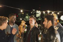 Young men drinking beer and talking at rooftop party — Stock Photo
