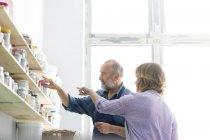 Mann und Frau stöbern im Kunstatelier in den Regalen — Stockfoto