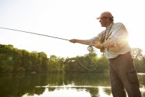 Senior man fly fishing at summer lake — Stock Photo