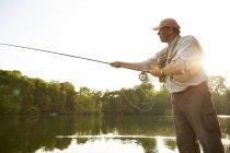 Homem sênior voar pesca no lago de verão — Fotografia de Stock
