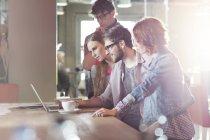 Gens d'affaires occasionnels travaillant à l'ordinateur portable au bureau ensoleillé — Photo de stock